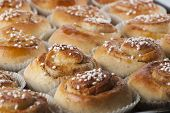 image of cinnamon  - Home baked cinnamon buns on a baking sheet.
