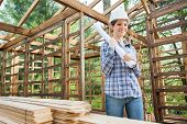 stock photo of timber  - Portrait of smiling female engineer holding blueprint while standing in incomplete timber cabin at construction site - JPG