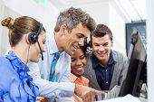 stock photo of telemarketing  - Manager with call center team using tablet PC in office - JPG