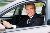 foto of only mature adults  - Cheerful mature man in formalwear driving car and smiling - JPG