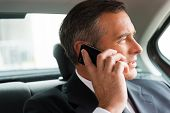 picture of only mature adults  - Confident mature businessman talking on the mobile phone and looking away while sitting on the back seat of a car - JPG