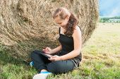stock photo of haystack  - Girl with device siting on the field close to haystack - JPG