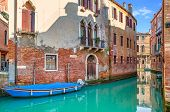 image of old boat  - Boat on narrow canal among old brick houses in Venice - JPG