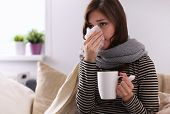 stock photo of epidemic  - Sick woman covered with blanket holding cup of tea sitting on sofa couch - JPG