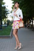 image of leggy  - Sexy young business woman talking on phone on the street - JPG