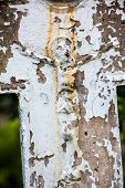 stock photo of crucifix  - Old crucifix gravestone with cracked whitewashed surface - JPG