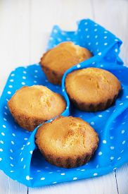 pic of bakeshop  - Homemade Muffins Ready for Breakfast on a napkin on wooden background - JPG