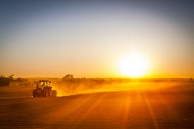 pic of farmer  - A farmer in a tractor prepares his field as the sun begins to set. The tractor is backlit by the setting sun. ** Note: Soft Focus at 100%, best at smaller sizes - JPG