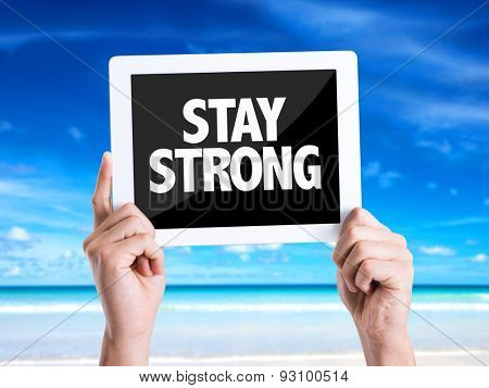 Tablet pc with text Stay Strong with beach background