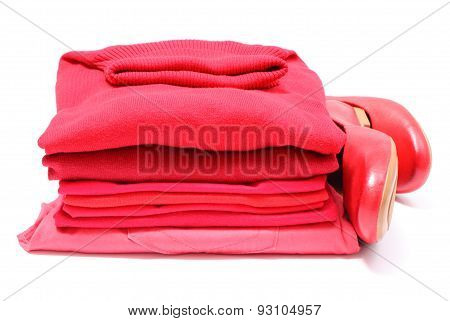 Womanly Shoes And Pile Of Red Clothes. White Background