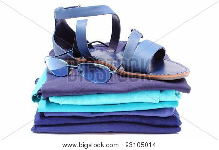 Womanly Sandals And Sunglasses On Pile Of Blue Clothes. White Background