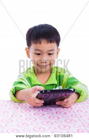 Little Asian (thai) Boy Using Digital Tablet At Desk