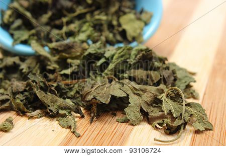 Heap Of Dried Nettle Pouring Out Of Blue Dish