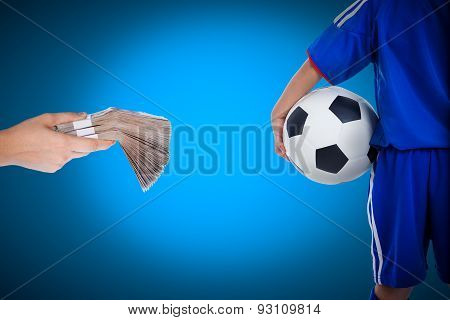 Back View Of Youth Soccer Player And Hand Holding Stacks Of Banknotes