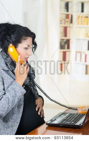 pregnant hispanic woman wearing casual clothes at work
