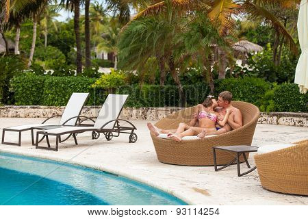 Husband And Wife Relaxing On Sunbeds At The Beach
