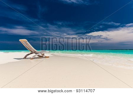 Tropical beach view of amazing water and empty chair on sand for relaxing vacations