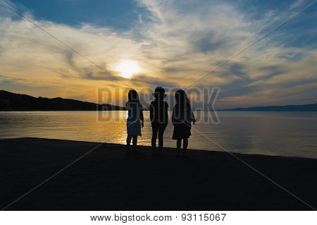 Three little girls watching the sunset against a dramatic sky.