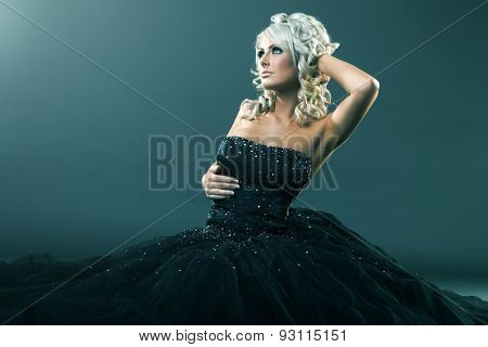 High fashion woman in sexy pose and  large formal dress sitting in studio