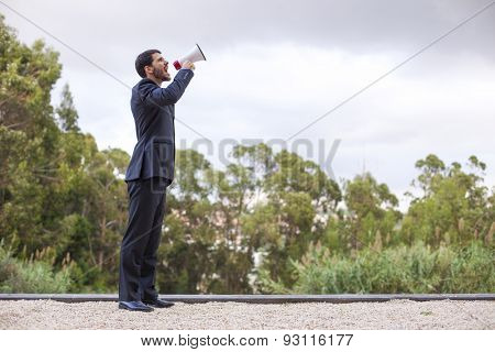 Businessman speaking at his megaphone