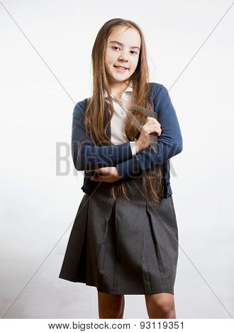Portrait Of Cute Smiling Schoolgirl Holding Plastic Ruler