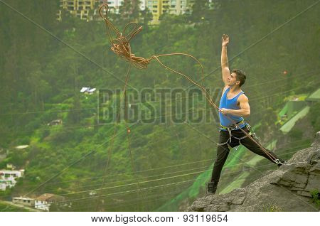 athletic man standing on cliff throwing rope down mountain