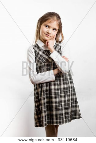 Thoughtful Schoolgirl In Uniform Posing Against White Background