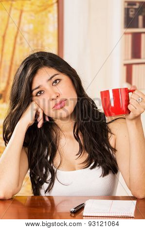 Hispanic girl sitting with coffee