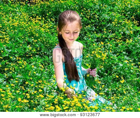 The Child Sits On A Glade With Flowers