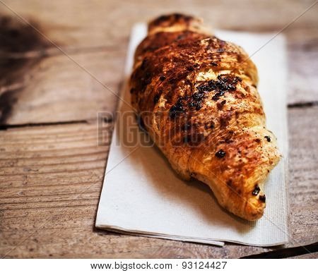 Fresh And Tasty Croissant Over Wooden Background For Breakfast. Chocolate Croissant Close Up.