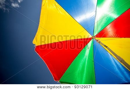 Closeup Of Colorful Sun Parasol On The Beach Against Blue Sky