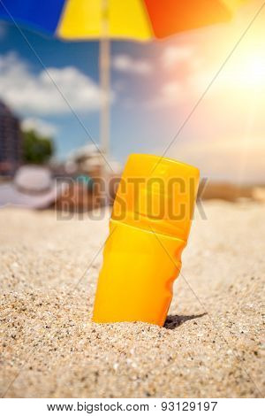 Closeup Of Yellow Suntan Lotion Bottle Lying On Sand At Beach