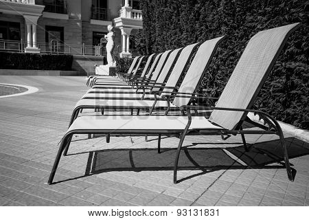 Black And White Shot Of Row Of Sunbed Chairs At Pool