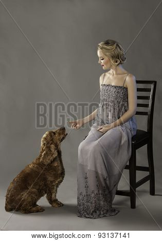 Portrait of beautiful blonde woman holding a treat for cute dog at her feet