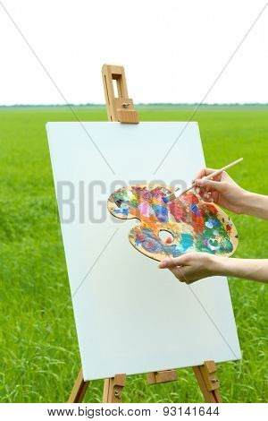 Female hand holding palette and easel with canvas in green field