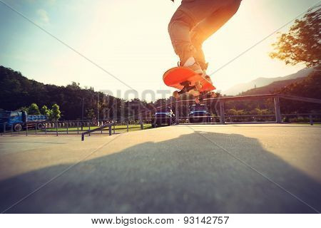 skateboarder legs doing a ollie at skatepark,vintage effect