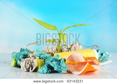 Pile of rubbish with plant on blue background