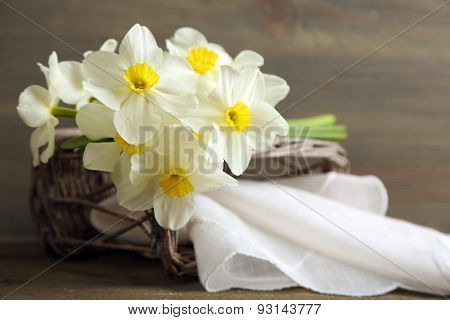 Fresh narcissus with wicker basket on wooden background