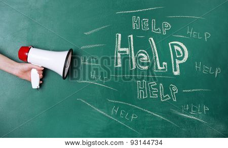 Hand holding megaphone on blackboard background