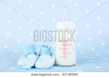 Baby milk bottle and babys bootees on blue background