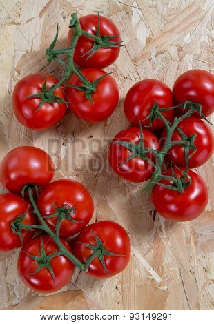 Fresh  Tomatoes On A Cluster Over Wooden  Table