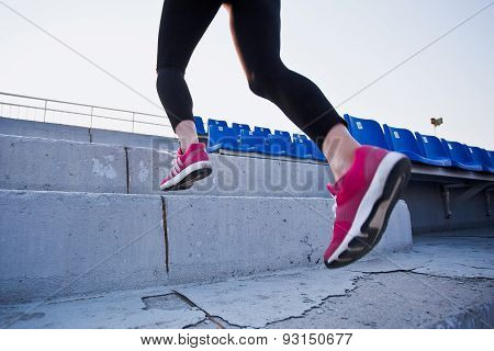 Close-up of young woman legs running to a sunset. Unrecognizable