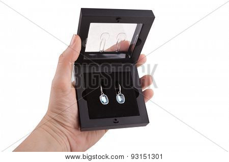Female hand holding a pair of sapphire earrings in a gift box, isolated on white background