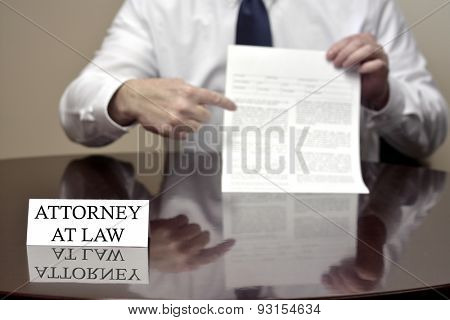 Attorney at Law sitting at desk holding blank document