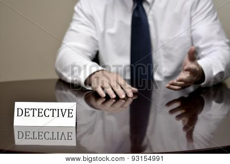 Detail of detective at desk with name sign hands