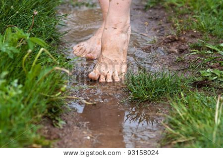 Feet Of A Young Woman Walking Through The Puddles After The Rain