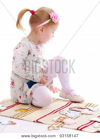 Little girl in a Montessori kindergarten playing sitting on the