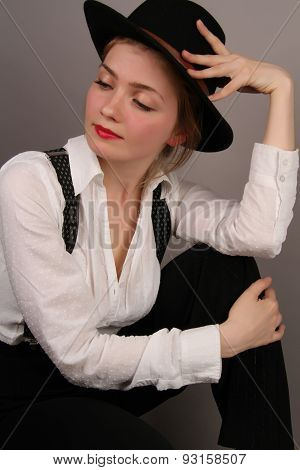portrait of the beautiful young girl in a suit and a hat