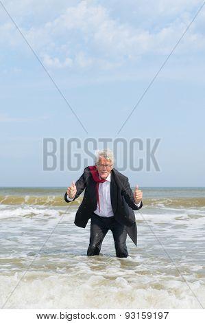 Senior business man standing in sea water