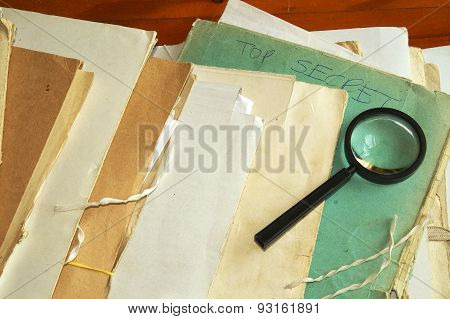 Vintage documents with magnifying glass investigation archives concept